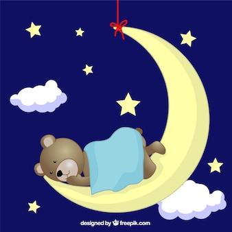 Urso de peluche que dorme na lua