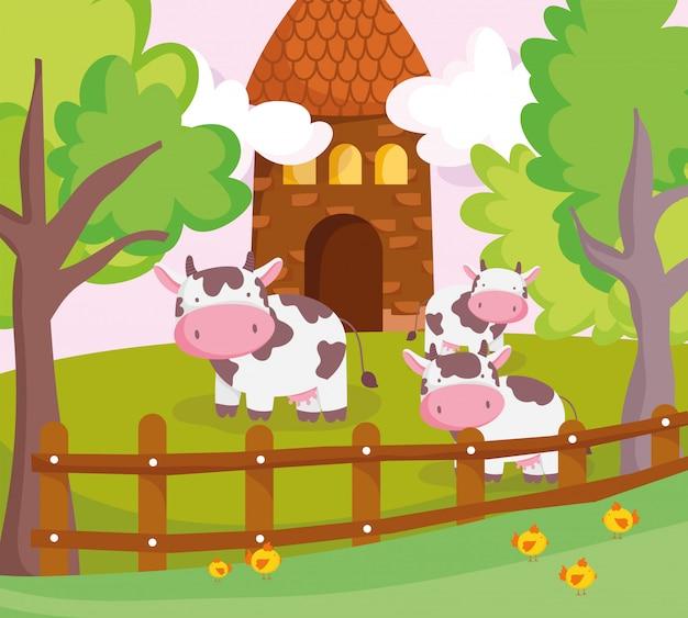 Vacas atrás de animais de fazenda cerca de madeira e celeiro