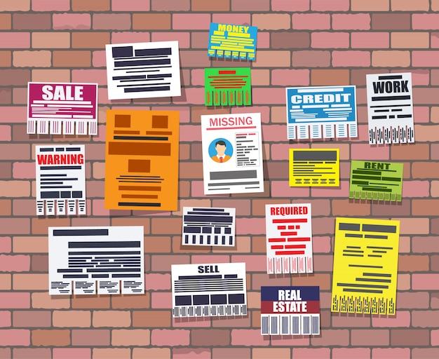 Vários anúncios de papéis destacáveis na parede de tijolo