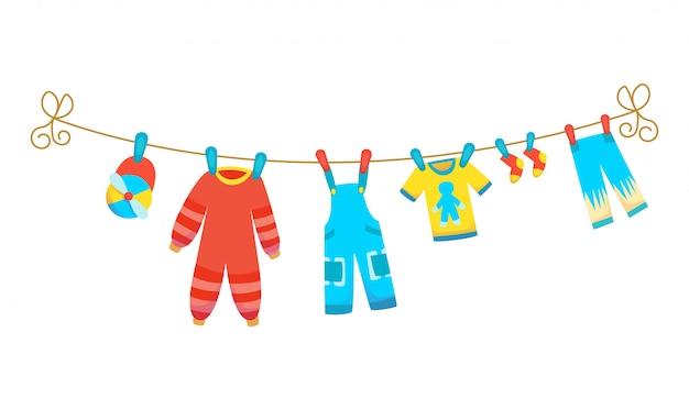 Vários itens de roupas de bebê na corda isolada. lavanderia realizada por estacas de plástico de secagem.