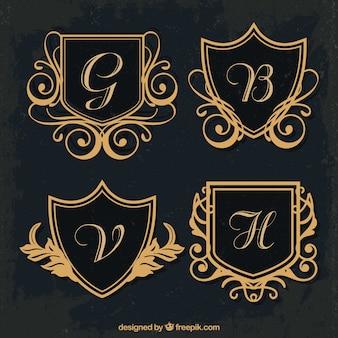 Vários monogramas de escudos dourados