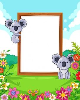 Vector a ilustração de coalas bonitos com sinal em branco de madeira no parque