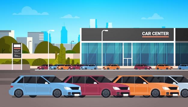 Veículos novos sobre o edifício da sala de exposições do centro do concessionário automóvel