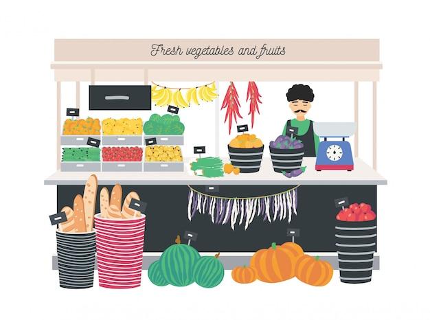 Vendedor de verdureiro em pé no balcão, tenda ou quiosque com escalas, frutas, legumes e pão.