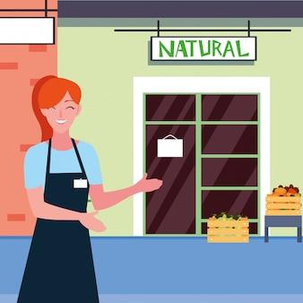 Vendedora com fachada de loja natural de frutas