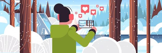 Viajante de mulher fotografando bosque nevado na câmera do smartphone