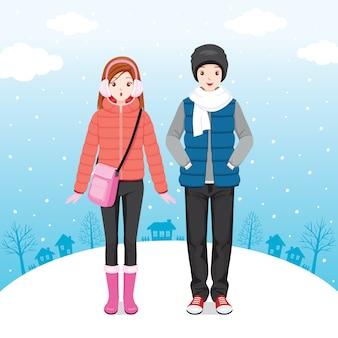 Viajante masculino e feminino, vestindo casaco de inverno, juntos na queda de neve
