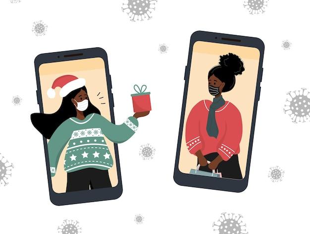 Videochamada de natal. namoradas africanas com máscaras compartilhando presentes online.