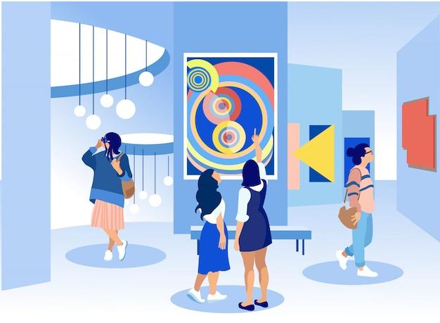 Visitantes da exposição visualizando pinturas na galeria.