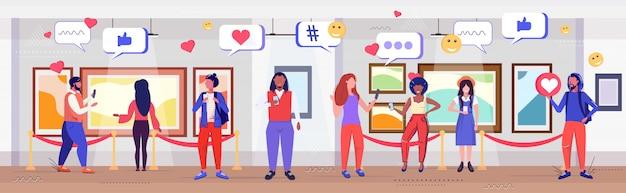 Visitantes que usam o aplicativo móvel on-line rede de mídia social bate-papo bolha comunicação conceito de dependência digital misturar pessoas de raça na galeria de arte moderna museu esboço comprimento total horizontal