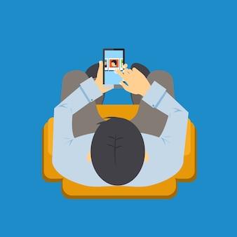 Vista aérea de um homem sentado em uma cadeira usando um aplicativo em seu telefone celular com a tela visível enquanto ele navega com o dedo.