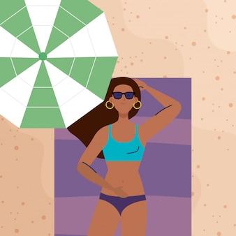 Vista aérea, mulher afro usando maiô deitado, bronzeamento na toalha, com guarda-chuva, na praia, temporada de férias de verão