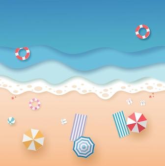 Vista de cima praia e mar com anel de natação, guarda-sóis e esteira no verão. conceito de arte de papel de vetor.