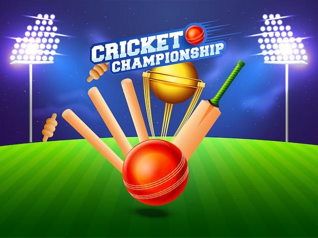 Vista próxima de wicket de grilo, bastão, bola e troféu de vencimento no fundo do estádio da noite.