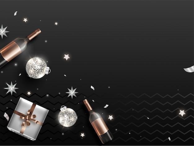Vista superior da caixa de presente, enfeites brilhantes, estrelas e garrafa de champanhe na faixa preta ondulada copyspace