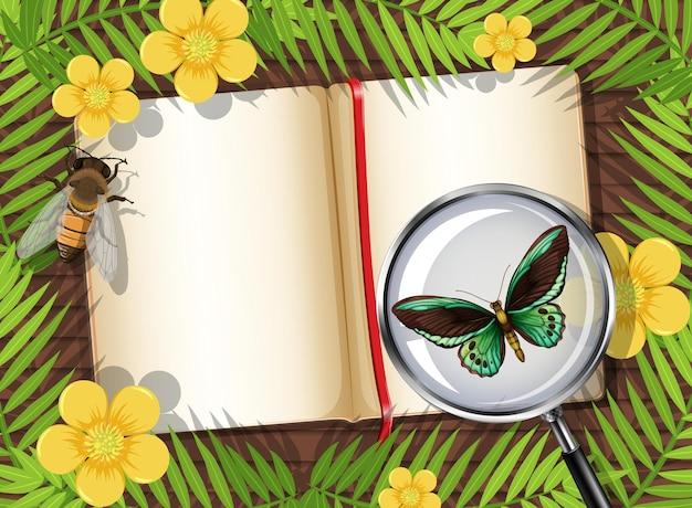 Vista superior da mesa de madeira com a página em branco do livro e o elemento insetos e folhas