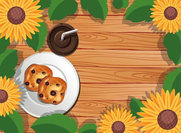 Vista superior da mesa de madeira com sobremesa e café gelado e folhas e elemento de girassol