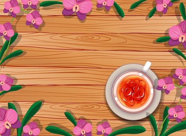 Vista superior da mesa de madeira em branco com uma xícara de chá, folhas e elemento orquídea rosa