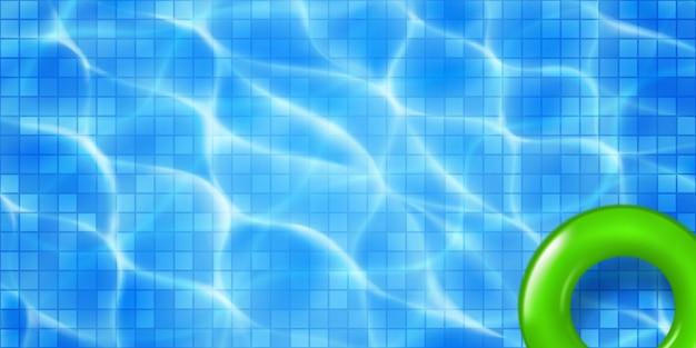 Vista superior da piscina com mosaico e aro inflável. superfície da água em tons de azul claro com reflexos de luz solar e ondulações cáusticas. fundo de férias de verão.