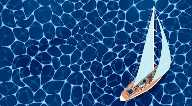 Vista superior do barco a vela na água do mar de um azul profundo