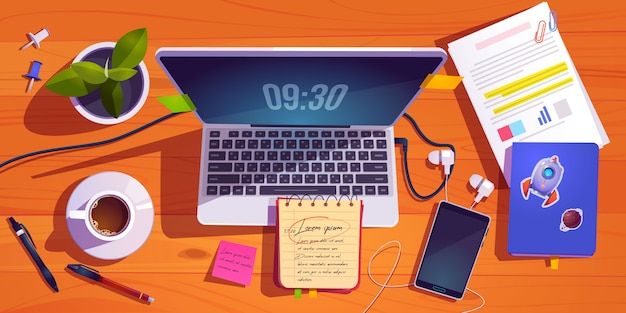 Vista superior do espaço de trabalho com laptop, artigos de papelaria, xícara de café e planta na mesa de madeira.
