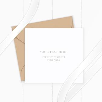 Vista superior envelope de papel kraft carta composição branca elegante e fita de seda com fundo de madeira.