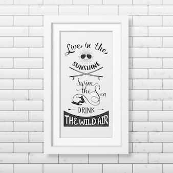 Viva o sol, nade o mar, beba o ar selvagem - cite o fundo tipográfico no quadro branco quadrado realista no fundo da parede de tijolo.