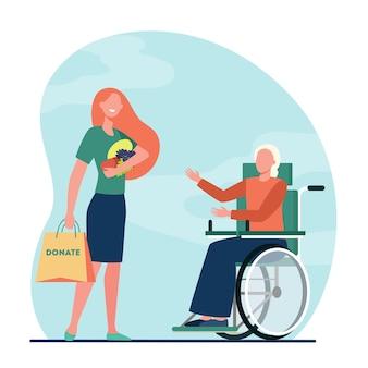 Voluntária levando comida para mulher com deficiência
