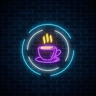 Xícara de café de néon brilhante cadastre-se em quadros de círculo sobre um fundo escuro da parede de tijolo. placa de rua à noite do café.