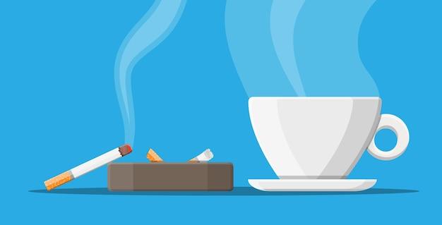 Xícara de café e cinzeiro cheio de cigarros fumados.