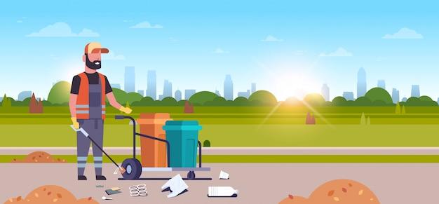 Zelador de homem, coleta de lixo com vara de ferro macho limpador empurrando carrinho carrinho