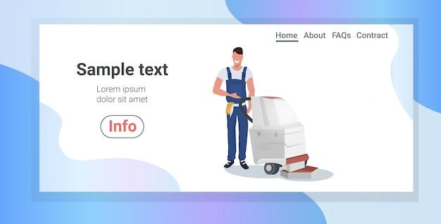 Zelador masculino usando aspirador de pó sorrindo homem em uniforme piso cuidados limpeza conceito horizontal comprimento total cópia espaço