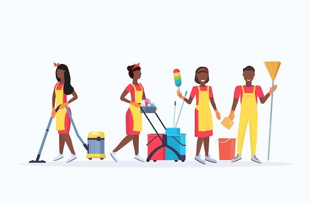 Zeladores, equipe, limpeza, serviço, conceito, americano africano, macho, femininas, produtos limpeza, uniforme, trabalhando, junto, com, equipamento profissional, apartamento, comprimento cheio comprimento