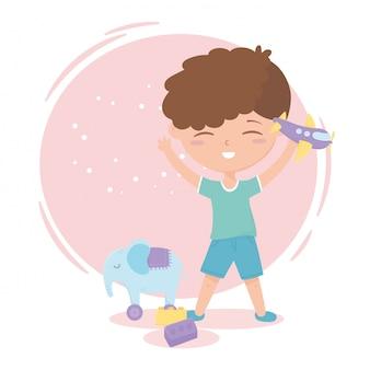 Zona de crianças, menino bonitinho com avião e elefante bloqueia brinquedos