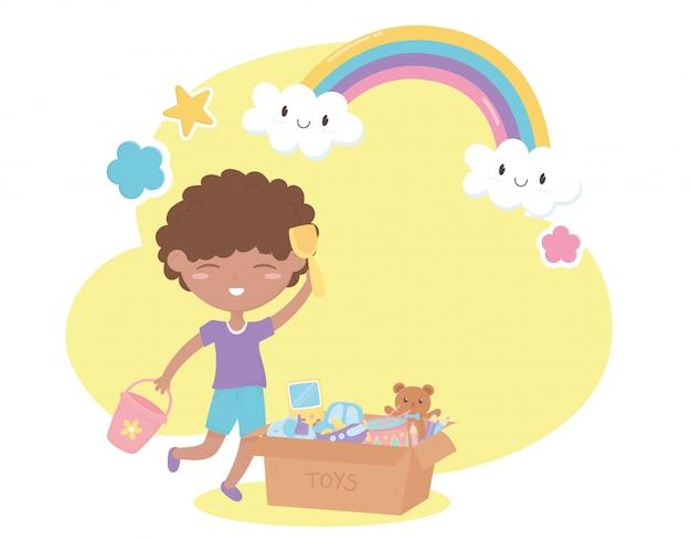 Zona de crianças, menino bonitinho com balde de pá e caixa de brinquedos