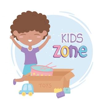 Zona de crianças, menino bonitinho com carro e caixa com brinquedos de blocos de tambor