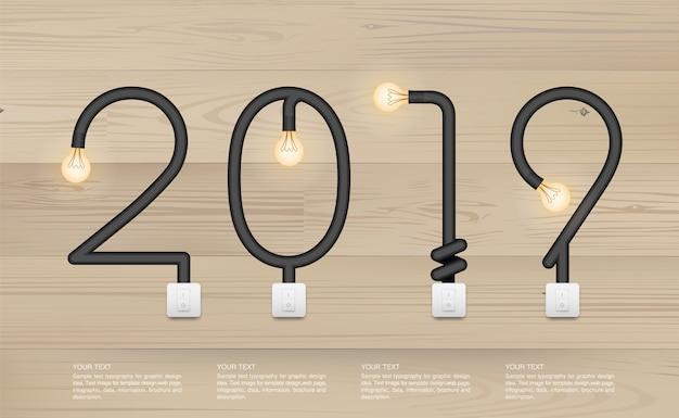 2019 - lampadina astratta su fondo di legno.