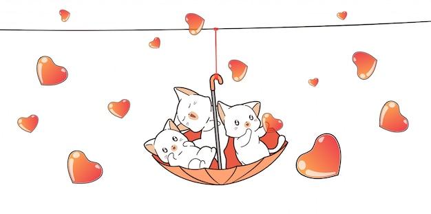 Adorabili gatti dentro l'ombrello rosso con i cuori