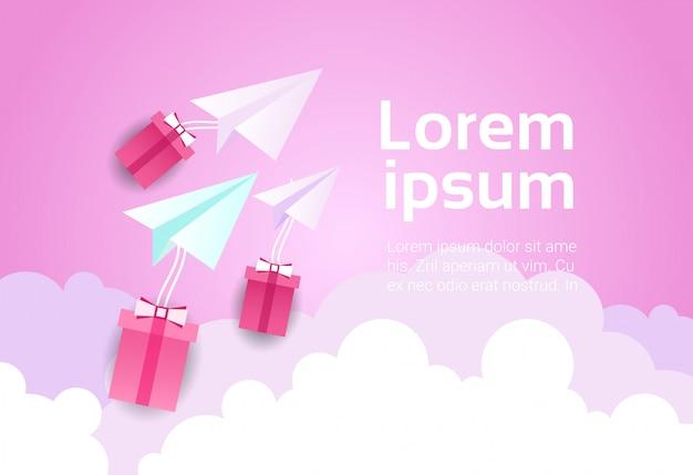 Aereo di carta in cielo sopra nuvole rosa e scatole regalo
