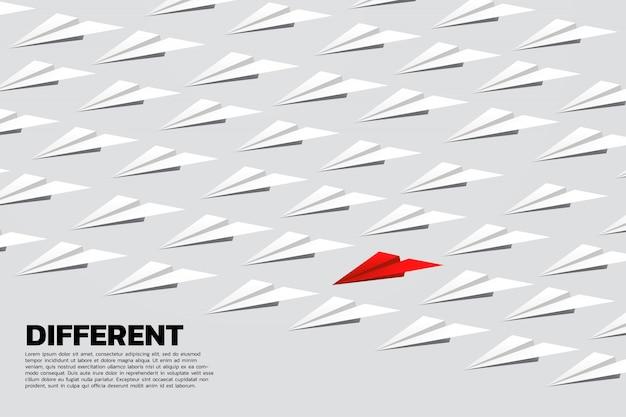 Aeroplano di carta origami rosso in gruppo di bianco. il concetto di affari di pensa la missione differente e di visione.