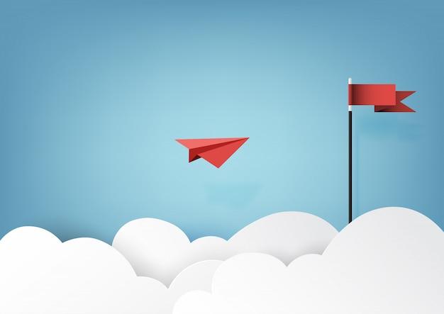 Aeroplano di carta rosso che vola alla bandiera rossa su cielo blu e nuvola.