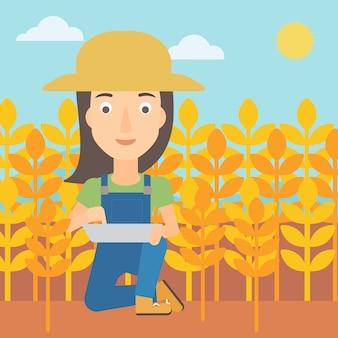 Agricoltore con computer tablet sul campo