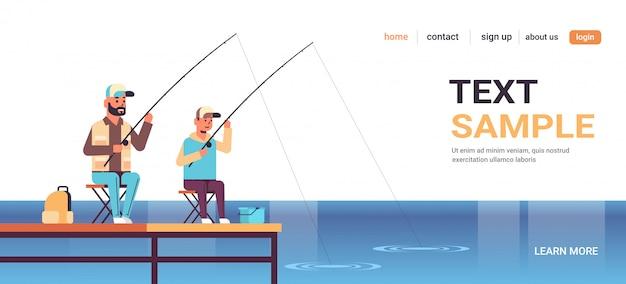 Amichevole padre e figlio pesca insieme dal molo uomo con ragazzino utilizzando canne seduto sul pontile in legno felice famiglia weekend pescatore concetto di hobby acqua orizzonte piatta piena lunghezza spazio di copia