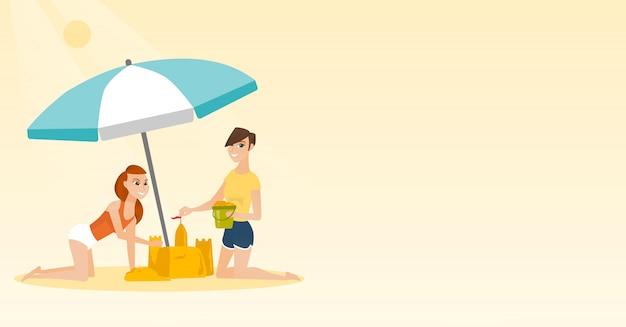 Amici che costruiscono un castello di sabbia sulla spiaggia