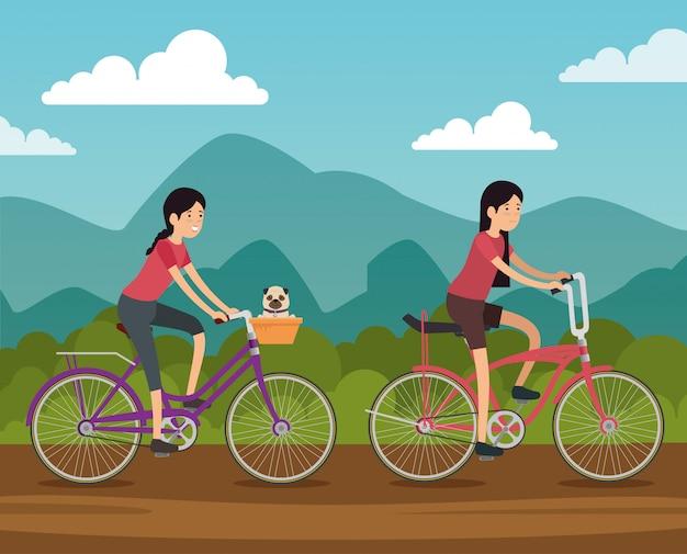 Amici di donne in sella a una bicicletta per fare esercizio