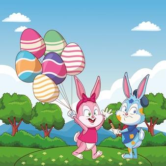 Amici felici del coniglietto di pasqua sveglio con gli impulsi dell'uovo sulla natura