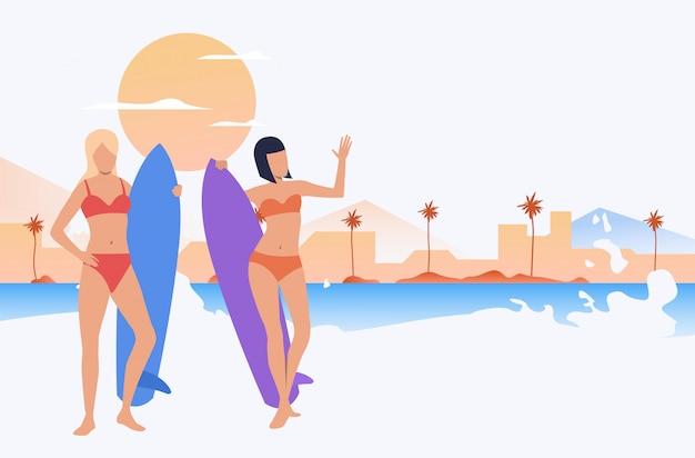 Amici femminili in costumi da bagno in piedi sulla spiaggia