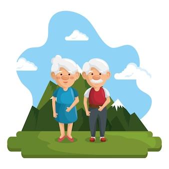 Anziani in piedi con montagne e cielo blu dietro