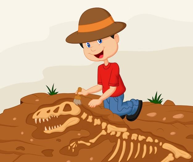 Archeologo del bambino che scava per il fossile di dinosauro