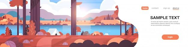 Area di campeggio tende nella foresta autunno campo concetto giornata di sole alba paesaggio natura con acqua montagne e colline